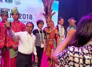 IFLA delegates take to the stage to pose for photos with Malay dancers.after the Opening Session