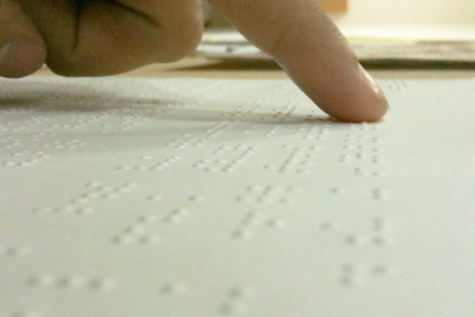 Fingertips reading a Braille manuscript