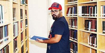 Yousef Al-Sayegh cataloging a book at the Khaldiya library, Kuwait