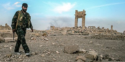 A Syrian government army soldier by the ruins of the Temple of Bel destroyed by ISIS militants in Palmyra, a UNESCO World Heritage site