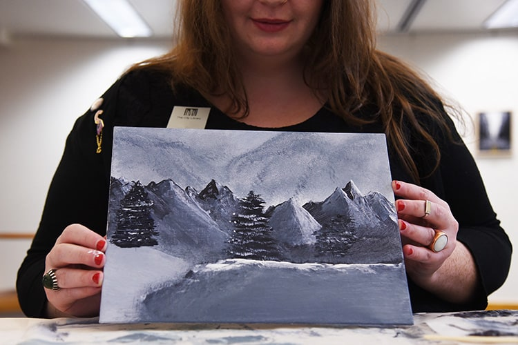 A participant shows off her finished work after a September Bob Ross Paint-Along event at the Salt Lake City Public Library's Sweet branch. Photo: Salt Lake City Public Library