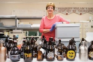 Judith A. Downie poses with growlers from CSUSM Library's Brewchive. Photo: Brandon Van Zanten (Brewchive)