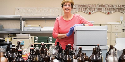Judith A. Downie poses with growlers from CSUSM Library's Brewchive. Photo by Brandon Van Zanten (Brewchive)