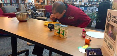 David Rush sets a new record at the Oak Brook Public Library by eating 241 kernels of corn with a toothpick in 3 minutes. Photo byChuck Fieldman / Pioneer Press