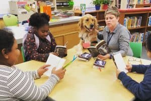 Kerri Price, a Charleston County (S.C.) Teacher Librarian Cohort member in University of South Carolina's Library Scholar program, works with students in her school library, alongside her therapy dog, Bailey.