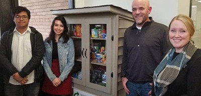 Bremen High School students, from left, Amner Diaz and Alyssa Ceballos stand with Jeff Eberhard and teacher Sarah Bogard at the school's new micropantry, which Eberhard donated in December. Photo by Jamie Bonnema
