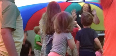 Katie Salo has fun with all the kids under the parachute in storytime