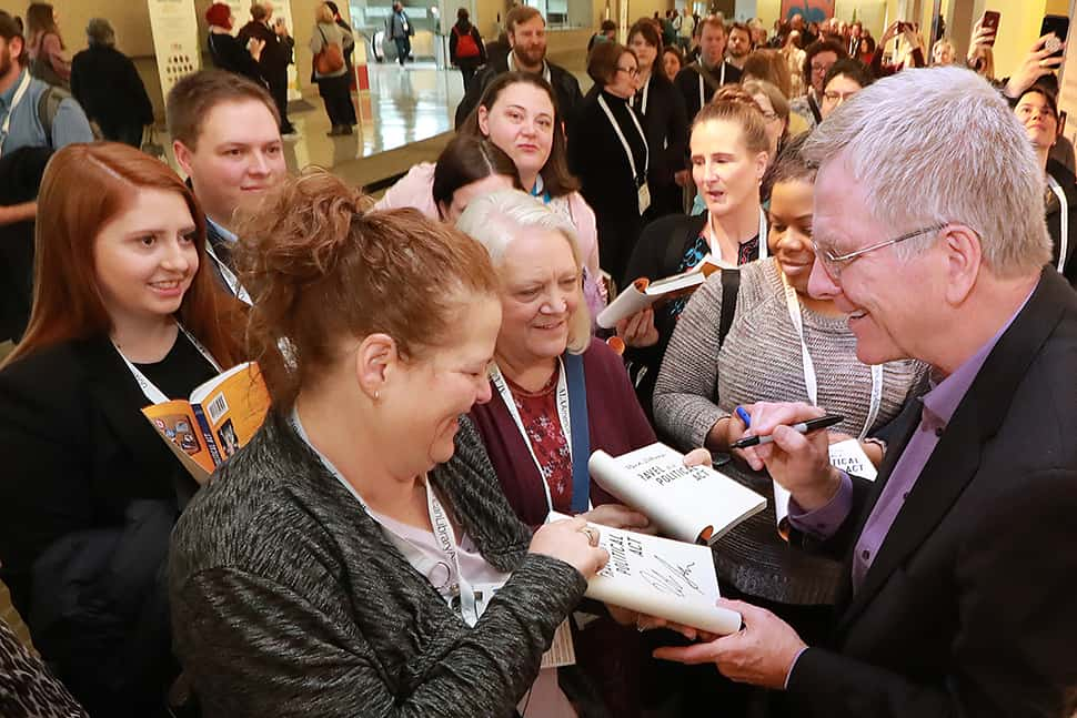 Attendees crowd around travel author Rick Steves for autographs following his Auditorium Speaker Series presentation at the 2019 ALA Midwinter Meeting. Photo: Cognotes