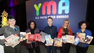 "From left: YALSA President Crystle Martin, Coretta Scott King Chair Claudette McLinn, ALSC President Jamie Campbell Naidoo, ALA President Loida Garcia-Febo, and Reforma President Madeline Pena Feliz at the 2019 ALA Youth Media Awards presentation. <span class=""credit"">Photo: Cognotes</span>"