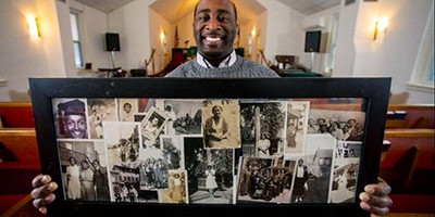 Winston Alozie holds a collage of images of past parishioners while at St. John's AME Zion Church in Bethlehem, Pennsylvania. Photo by Rick Kintzel, Allentown Morning Call