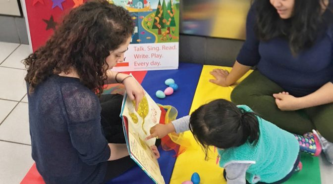 Chicago Public Library STEAM Team First Assistant Librarian Alejandra Santana (left) reads to storytime attendees at Bubbleland laundromat.Photo: Chicago Public Library