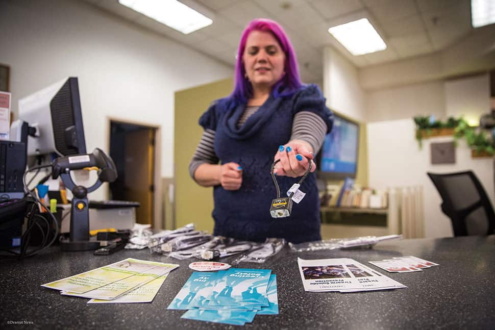Stephanie Jewett, manager at Salt Lake County Library's Columbus branch, displays a gun lock available at the library. (Photo: Qiling Wang/Deseret News)