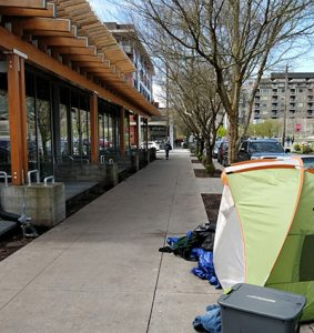 A tent sits outside of Seattle Public Library's Ballard branch. The library installed exterior metal bars to discourage loitering. (Photo: Alanna Ho)