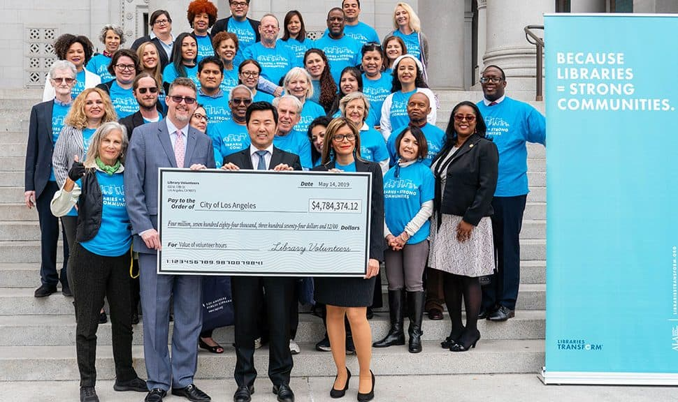 Los Angeles City Librarian John Szabo (front row, from left), Councilmember David Ryu, and ALA President Loida Garcia-Febo hold a giant check for nearly $4.8 million, symbolizing the efforts of the nearly 7,500 volunteers who contributed 164,000 hours of work in Los Angeles Public Library's 73 locations in 2018. Photo: Los Angeles Public Library