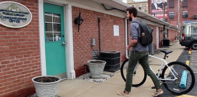Communications Specialist Corey Weberling bikes to work for Bike to Work Week. Screenshot from video