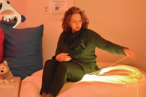 A Louisville (Ohio) Public Library patron uses an LED softie, a large beanbag cushion with an integrated light source and fiber optics, that produces a calming effect. (Photo: Michael Damron)