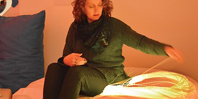 A Louisville (Ohio) Public Library patron uses an LED softie, a large beanbag cushion with an integrated light source and fiber optics, that produces a calming effect. Photo by Michael Damron