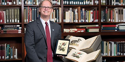 Martin R. Kalfatovic is holding the digitized version of Edward Donovan's An Epitome of the Natural History of the Insects of New Holland, New Zealand, New Guinea, Otaheite, and Other Islands in the Indian, Southern, and Pacific Oceans (1805). Photo by Aaron Clamage