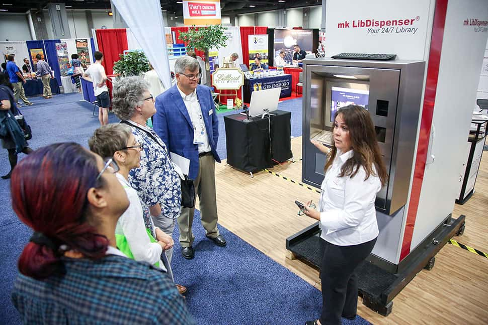 A rep with mk Solutions demonstrates the mk LibDispenser in the 2019 ALA Annual Conference Exhibit Hall. Photo: Cognotes