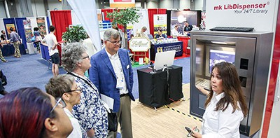 A rep with mk Solutions demonstrates the mk LibDispenser in the 2019 ALA Annual Conference Exhibit Hall