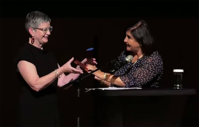 Incoming IFLA President Christine Mackenzie (left) accepts the gavel from outgoing President Glòria Pérez-Salmerón during the Closing Session in Athens, Greece, August 29.