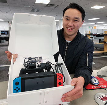 A student employee at University of Utah's J. Willard Marriott Library displays a Nintendo Switch that can be checked out and played at the library. Photo: Jordan Hanzon