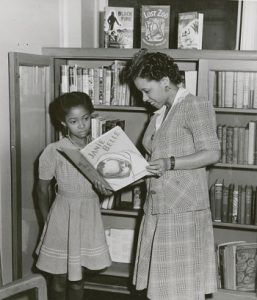 "Librarian Augusta Baker showing a copy of Ellen Tarry's ""Janie Belle"" to a young girl, at the 135th Street (now Countee Cullen) Branch Library of the New York Public Library in Harlem, New York, around 1941. Courtesy NYPL"