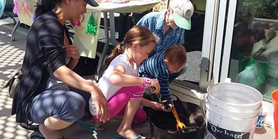 Master Gardener Susan McCorry (in white hat) helps a family gather compost for their seed bombs at the Pico branch of the Santa Monica (Calif.) Public Library system for the library's ClimateFest program in April 2017. Photo by Jen Ullrich