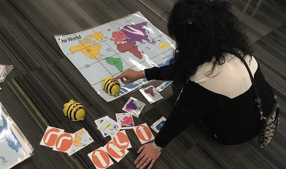 A librarian uses a Bee Bot at Do the Bot—Librarians Using Robots to Impact Learning at AASL 2019. Photo: Phil Morehart