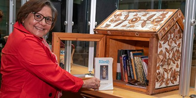 NMAI librarian Elayne Silversmith shares a book in the birchbark Little Free Library