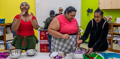 Adeeba Rana, center, helps two students during a cooking class at the Cypress Hills branch of the Brooklyn Public Library. Photo by Brittainy Newman / The New York Times