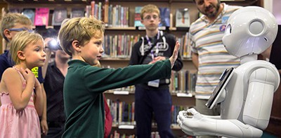 Children interact with Pepper the robot at the Central Rappahannock (Va.) Regional Library. Photo by Peter Cihelka