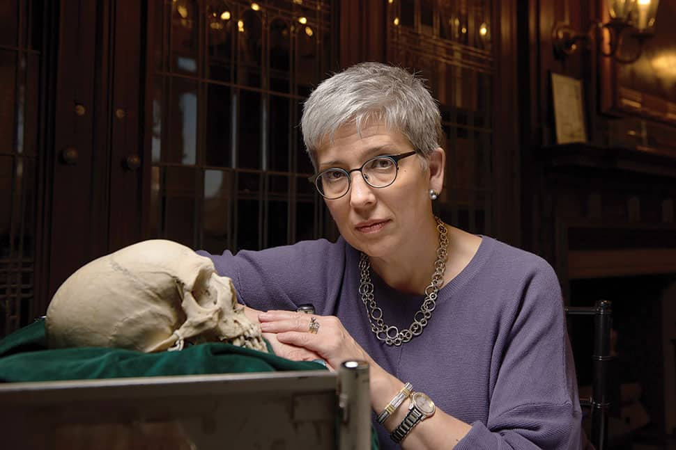 Beth M. Lander, college librarian at the Historical Medical Library of the College of Physicians of Philadelphia, poses with a human skull set on green velvet. (Photo: Kriston Bethel)