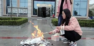 Two library employees burn books in front of the public library in Zhenyuan, Gansu province