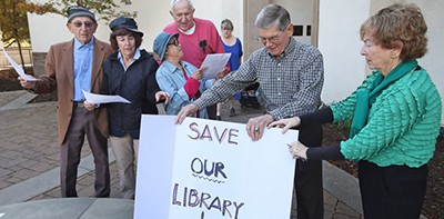 Julie Davey and her husband Bob, on right, with supporters in front of the Laguna Niguel Library. Photo by Don Leach