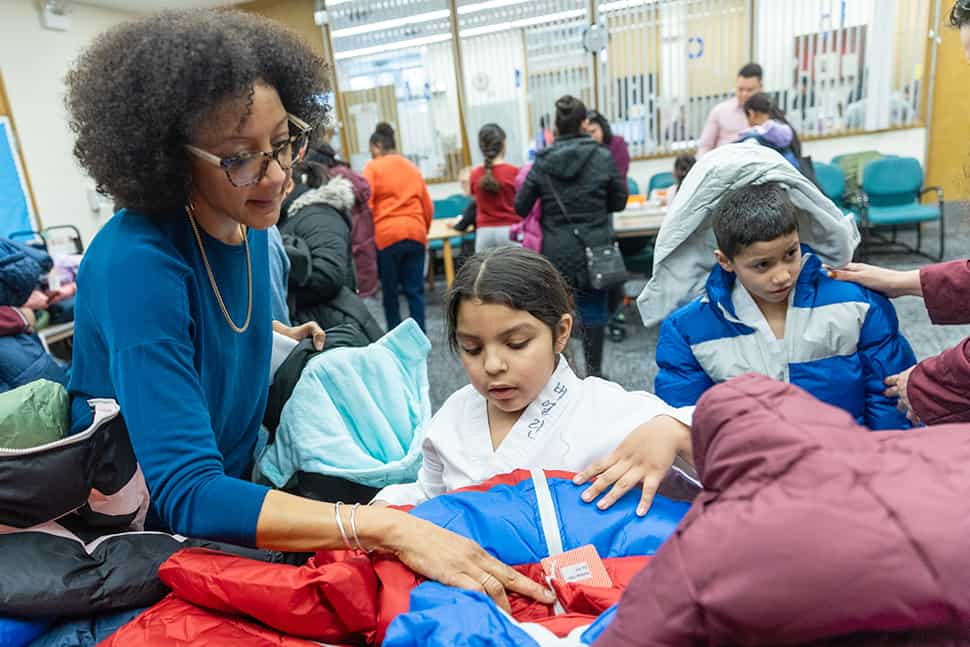 A librarian helps a child pick out her new coat at Chicago Public Library's Chicago Lawn branch. (Photo: Francis Son)