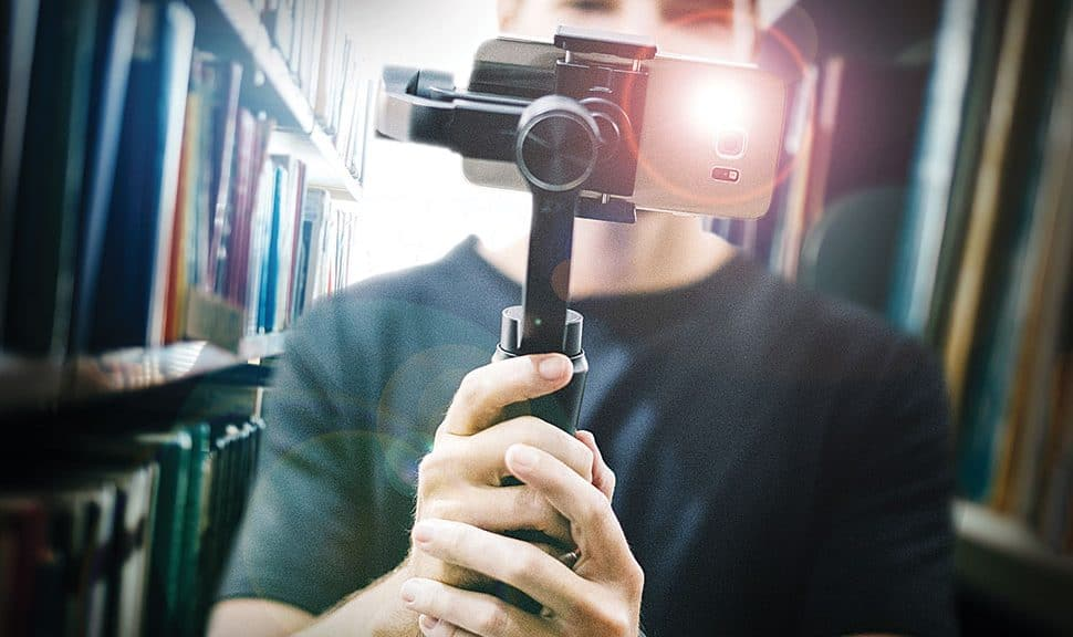 Photo: Man holding a video camera in the library