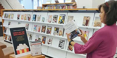 Leah Elzner, a staff member at Mandel Public Library in West Palm Beach, Florida, looks over the latest binge bundles