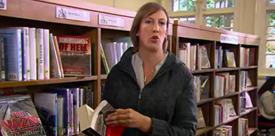 Screenshot from the British TV show Miranda, season 2, episode 2. Miranda has a shushing battle with the librarian