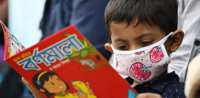 Boy with mask reading. Photo by Mehedi Hasan / NurPhoto via Getty Images