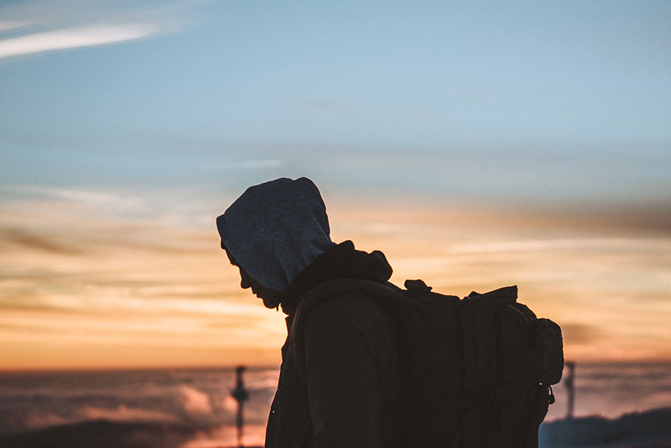 Photo: Silhouette of man with backpack against sunset
