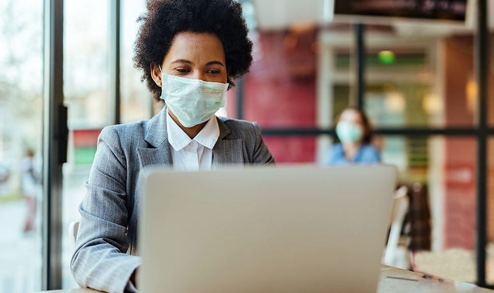 Woman wearing a face mask with a laptop