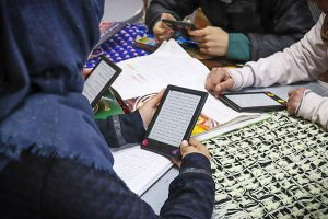Photo: Refugees reading on Kindles