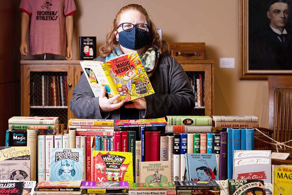Amy Schindler, director of archives and special collections at University of Nebraska at Omaha (UNO) Libraries, holds a magic book from the Omaha (Neb.) Magical Society collection. (Photo: University of Nebraska at Omaha)