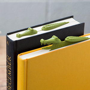 Plastic crocodile-shaped bookmark in book