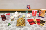 The Masterpiece Book Club at Chicago Public Library's Vodak–East Side branch hosted a Miss Fisher–themed holiday party in 2015. (Photo: Table set with books, postcards, teapot, scones, and Union Jack flags)