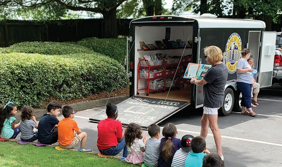 Valerie Wagley, counselor at Fair Oaks Elementary School in Cobb County, Georgia, reads to kids at a bookmobile stop in summer 2020. Photo: Kelli Wood