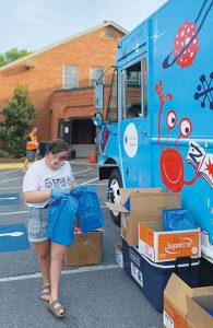 "Reading to Go Places volunteer Madison Cowart distributes books and meals at a stop in Bartow County, Georgia, in April 2020. <span class=""credit"">Photo: Reading to Go Places</span>"