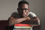 Young Black man wearing glasses, with arms folded on stack of books (Photo: Oladimeji Ajegbile/Pexels)