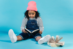Cute Black girl wearing striped shirt and overalls sits on floor and reads storybooks (Photo: Amina Filkins/Pexels)